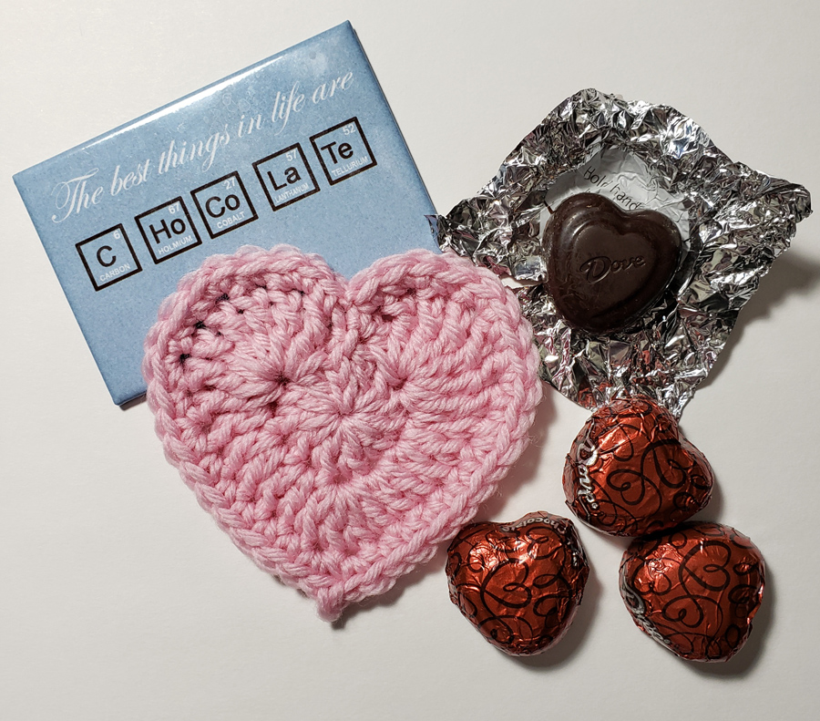 Crocheted Bordered Heart in light pink yarn with Dove chocolate hearts wrapped and unwrapped and a blue rectangle with Chocolate spelt using periodic table element abbreviations.