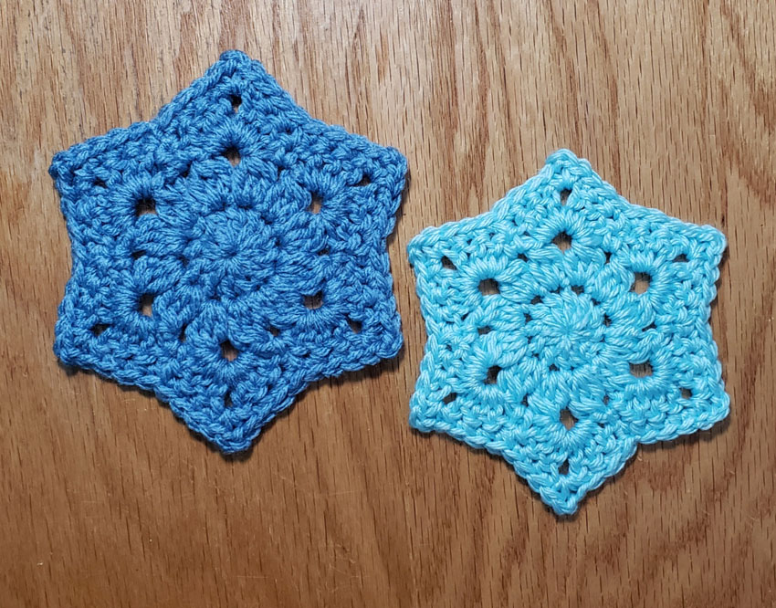 2 motifs side by side. Darker blue one on left larger than light blue one on right.