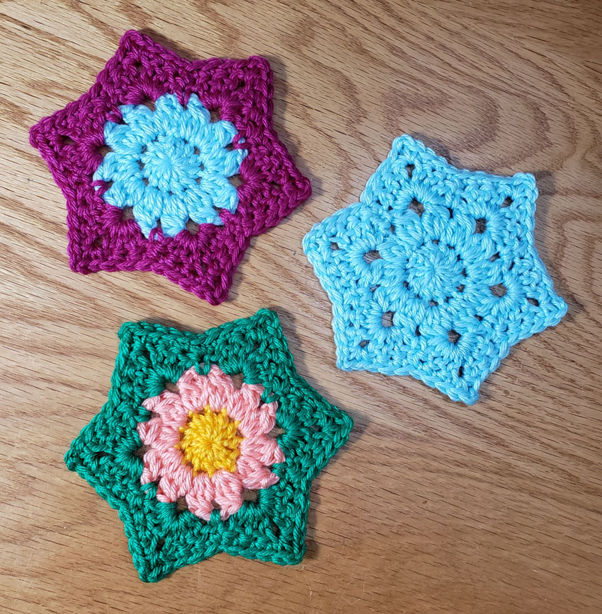 3 hexagonal crocheted motifs, 1 in single color of light blue, 1 in 2 colors of light blue in center with violet outside, 1 with yellow center surrounded by peach colored petals finished with bright green as leaves.
